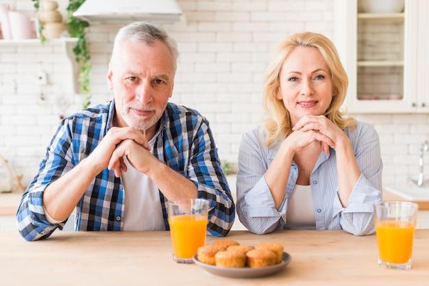 ジュースグラスとマフィンのテーブルの上に笑みを浮かべて年配のカップルの肖像画