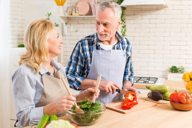 Пожилая пара готовит салат в современной кухне, глядя друг на друга