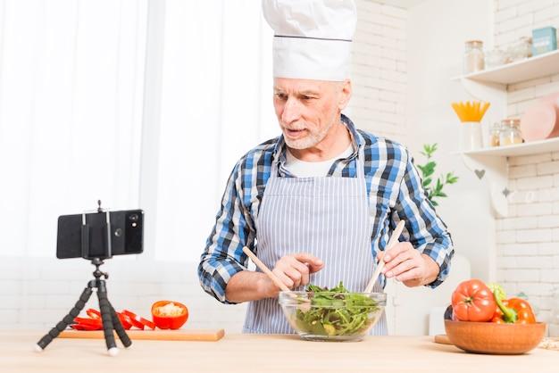 年配の男性が台所でサラダを準備しながら携帯電話を見て
