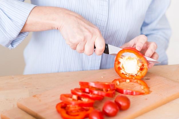 Крупным планом женской руки, резка ломтик красного перца с ножом на разделочную доску