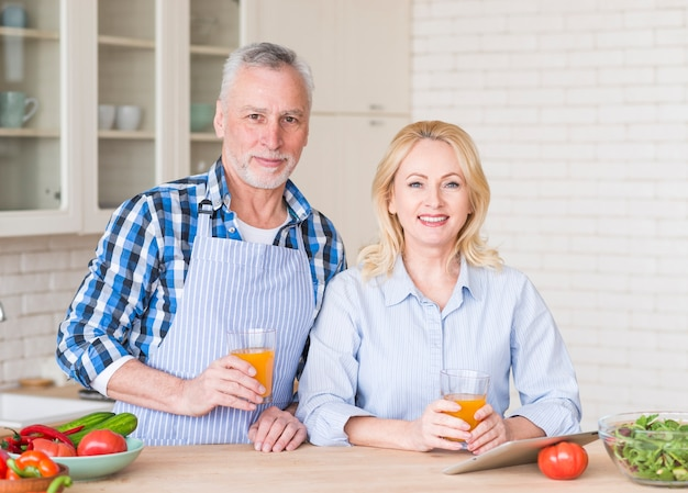 デジタルタブレットと野菜の木製テーブルの上のジュースのガラスを保持している年配のカップルの肖像画
