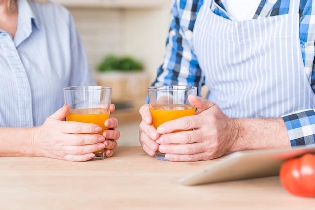 木製のテーブルにジュースのガラスを保持している年配のカップルのクローズアップ