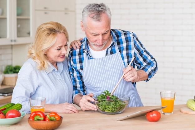 デジタルタブレットを見てグリーンサラダを準備する彼女の夫を見ている年配の女性
