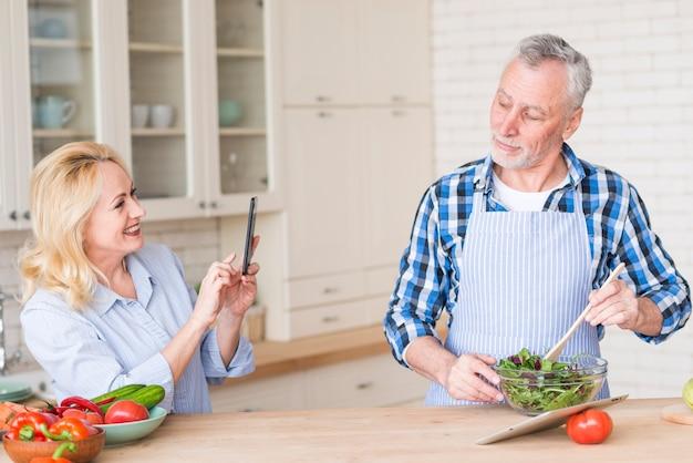 幸せな年配の女性がボウルにサラダを準備する彼女の夫の写真を撮る