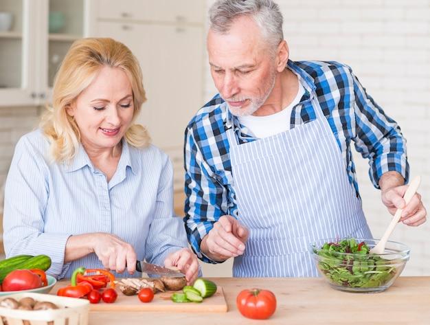 Усмехаясь старший человек помогая ее жене в подготовке салата на кухне