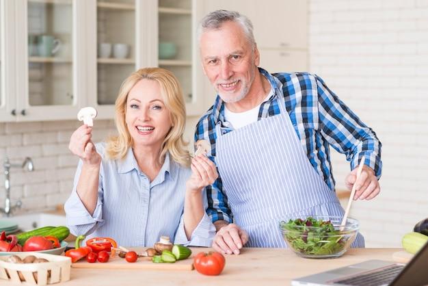 木製の机の上の野菜サラダを準備する笑顔の年配のカップルの肖像画