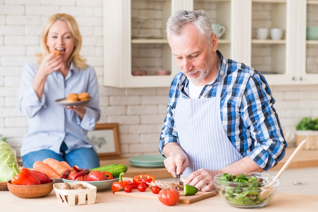 Старший мужчина резки овощей на разделочную доску с женой, ест кексы на фоне на кухне