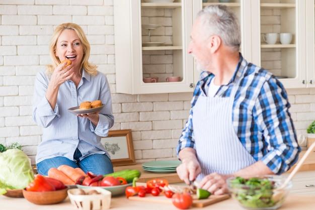 Старший мужчина нарезка овощей на разделочную доску, глядя на ее жена ест кексы на кухне