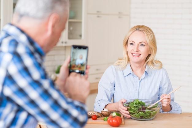 ガラスのボウルに新鮮なサラダを準備する彼女の妻の写真を撮る年配の男性人のクローズアップ
