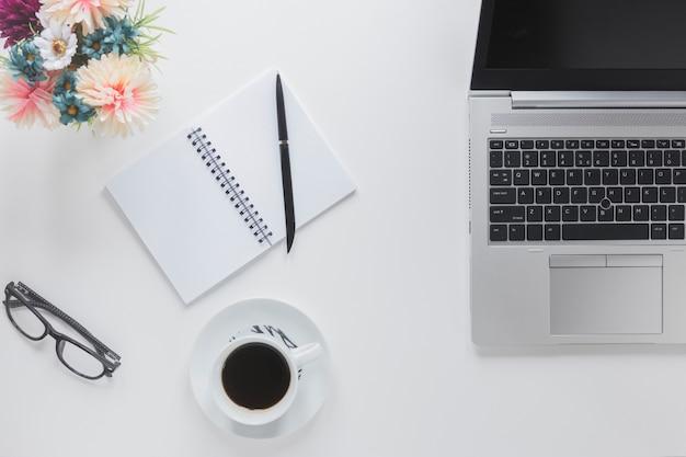 Ноутбук возле канцелярских принадлежностей и чашка кофе