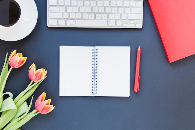 コーヒーカップとチューリップの花の机の上のキーボードの近くのノートブックを開く
