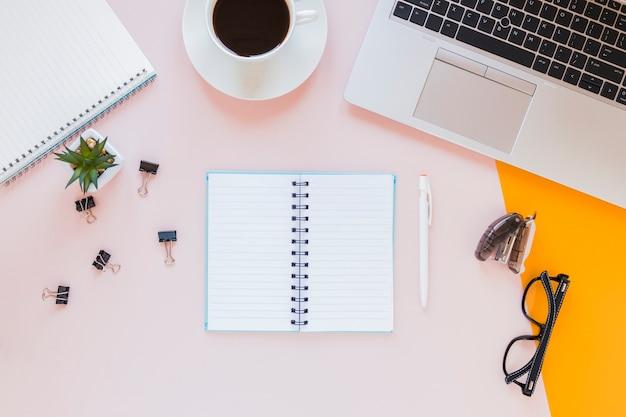 コーヒーカップと文房具とピンクの机の上の眼鏡の近くでノートブックを開く