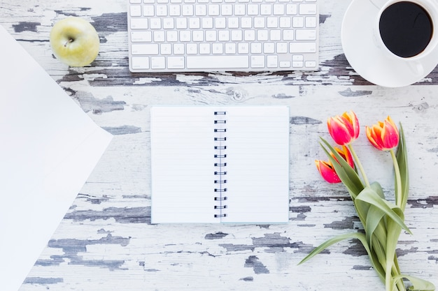 みすぼらしい机の上のキーボードとコーヒーカップの近くに開いたノートとチューリップの花
