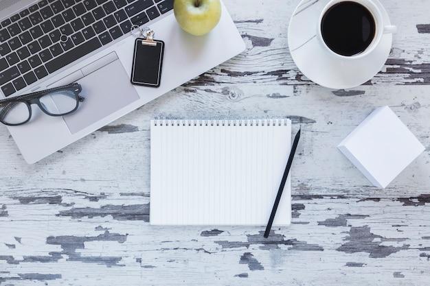 Блокнот с карандашом возле ноутбука и кофейной чашки