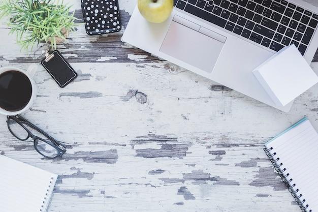 Ноутбук и канцелярские принадлежности возле чашки кофе и очки