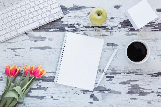 汚れた机の上のキーボードとチューリップの花の近くのノートとコーヒーカップ