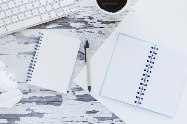 汚れた机の上のキーボードとコーヒーカップの近くのノートブックとヘッドフォン
