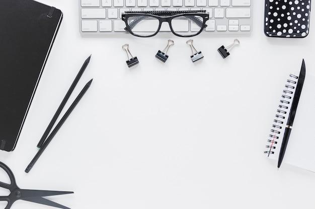 Рабочее место с канцелярскими и очки на клавиатуре