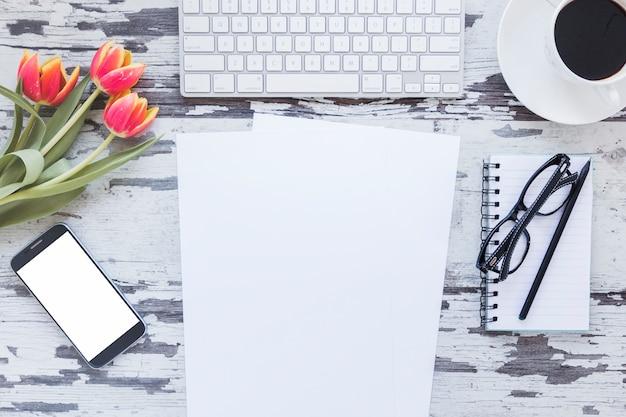 紙とキーボードとコーヒーカップの近くの空の画面を持つスマートフォン