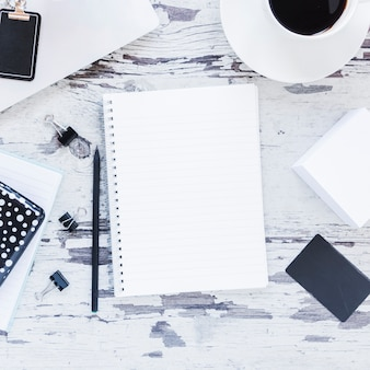 文房具と汚れた机の上のコーヒーカップ