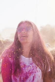 Красивая женщина покрыта розовыми и желтыми цветами холи
