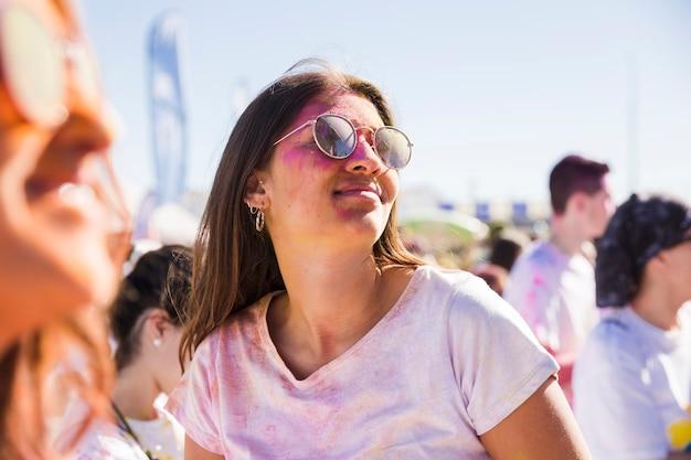 ホーリーカラーで遊ぶサングラスをかけている女性のクローズアップ