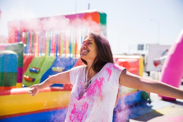 Улыбается молодая женщина, наслаждаясь цветом холи