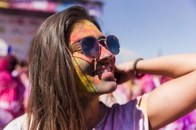 Улыбающаяся молодая женщина в темных очках, покрытых красками холи