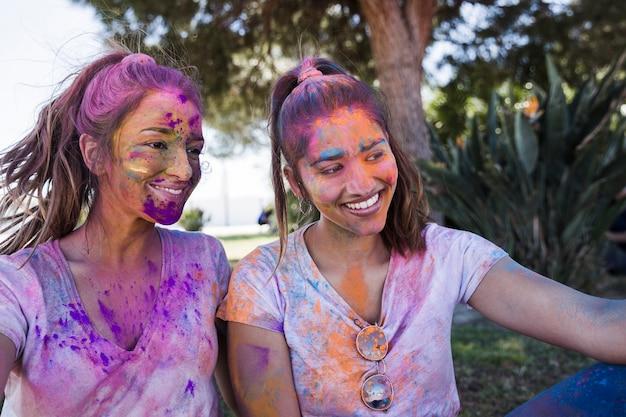 Молодая женщина с подругой покрыты порошком холи, принимая селфи на мобильный
