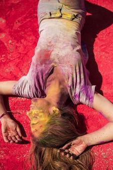Поднятый вид молодых женщин, лежащих на холи цвета