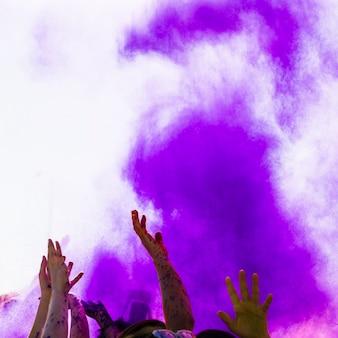 Фиолетовый цвет холи над людьми, поднимающими руку, танцует