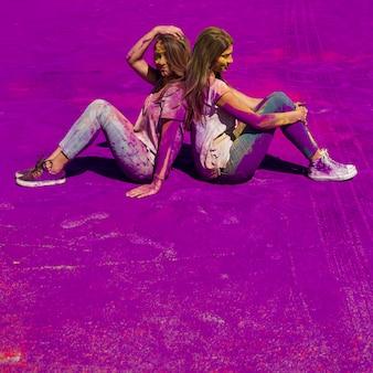 紫色のホーリー色の上に背中合わせに座っている若い女性
