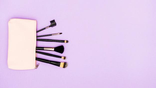 Черные кисти для макияжа в бежевой сумке на фиолетовом фоне