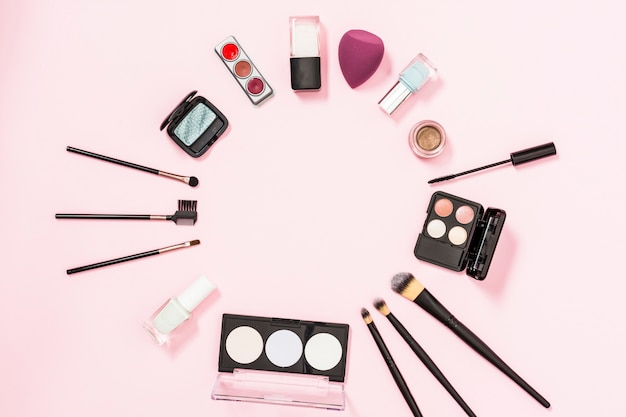 Круглая рамка с кисточками для макияжа; бутылка лака для ногтей; тени для век; блендер на розовом фоне