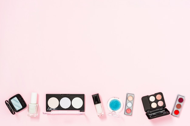 Косметическая палитра с бутылками лака для ногтей на розовом фоне