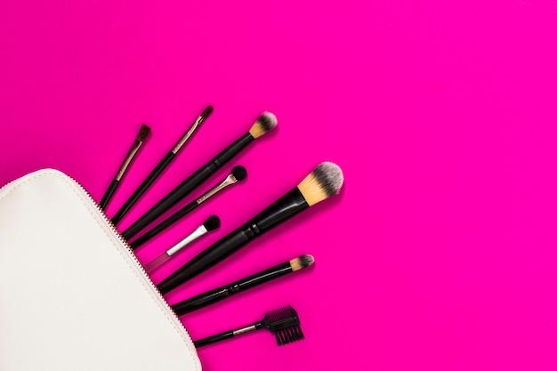 ピンクの背景の上の白い袋から多くの化粧ブラシ