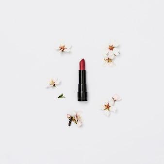 Красная помада с веточкой весеннего цветения на белом фоне