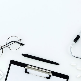 めがねペン;クリップボード薬と白い背景の上の聴診器