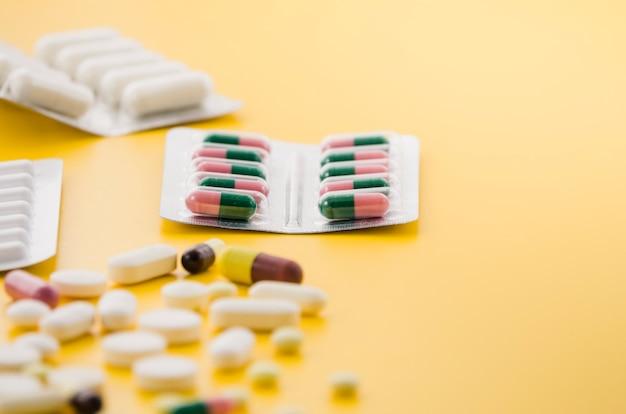 黄色の背景に多くの錠剤ブリスターパック