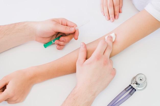 白い机の上に注射器を与えた後、患者の手の上に綿を保持している医師の手のクローズアップ