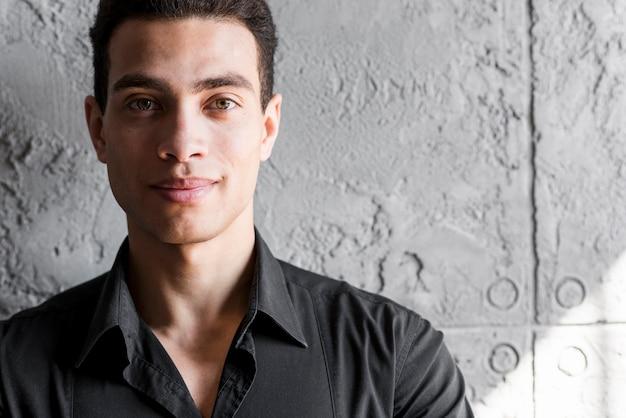壁に立っている笑顔の若い男の肖像