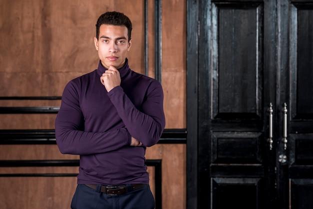 Портрет красивый молодой человек с его руку на подбородке, стоя у деревянной стены