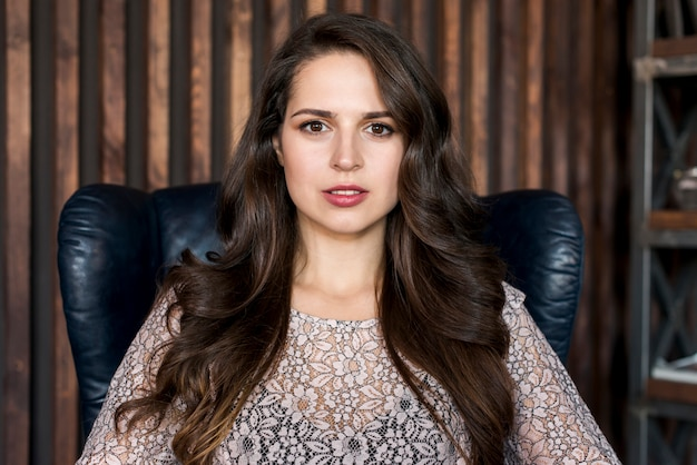 カメラ目線の肘掛け椅子に座って美しい若い女性の肖像画