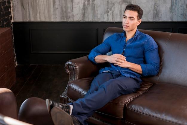 Молодой человек, сидя на диване со скрещенными ногами и сложив руки, глядя в сторону