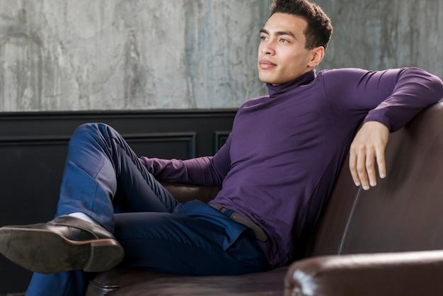 スタイリッシュなハンサムな若い男が離れているソファーでリラックス