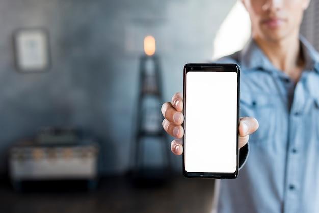 白い画面表示スマートフォンを手に見せて男のクローズアップ