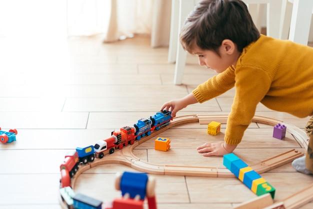 Малыш играет с игрушечным поездом