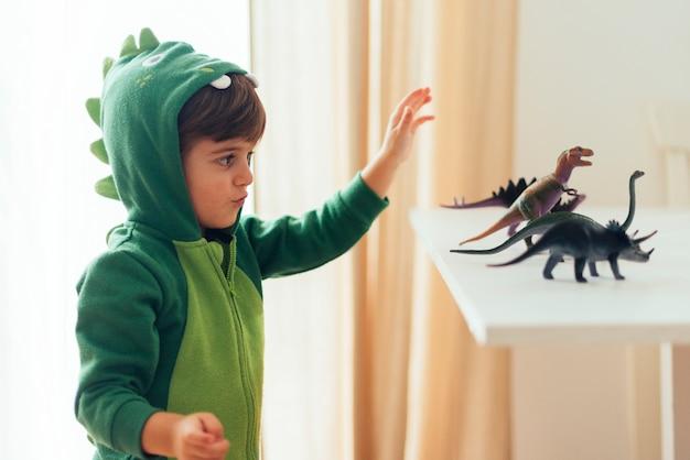 Малыш играет с игрушечными динозаврами