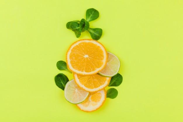 薄緑色の背景の葉と柑橘系の果物のスライス
