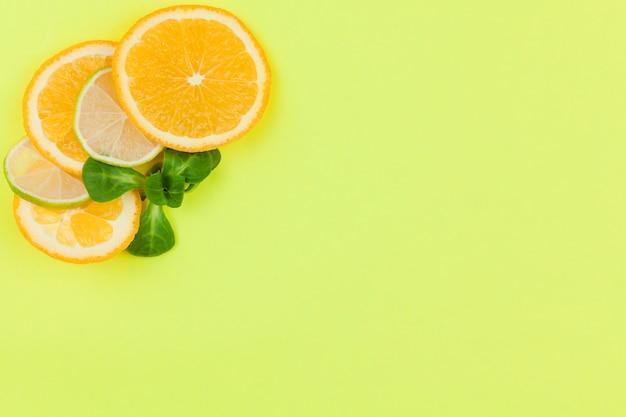 明るい背景に柑橘系の果物と緑の葉を切る